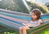 Little girl sitting on hammock in the garden reading a book