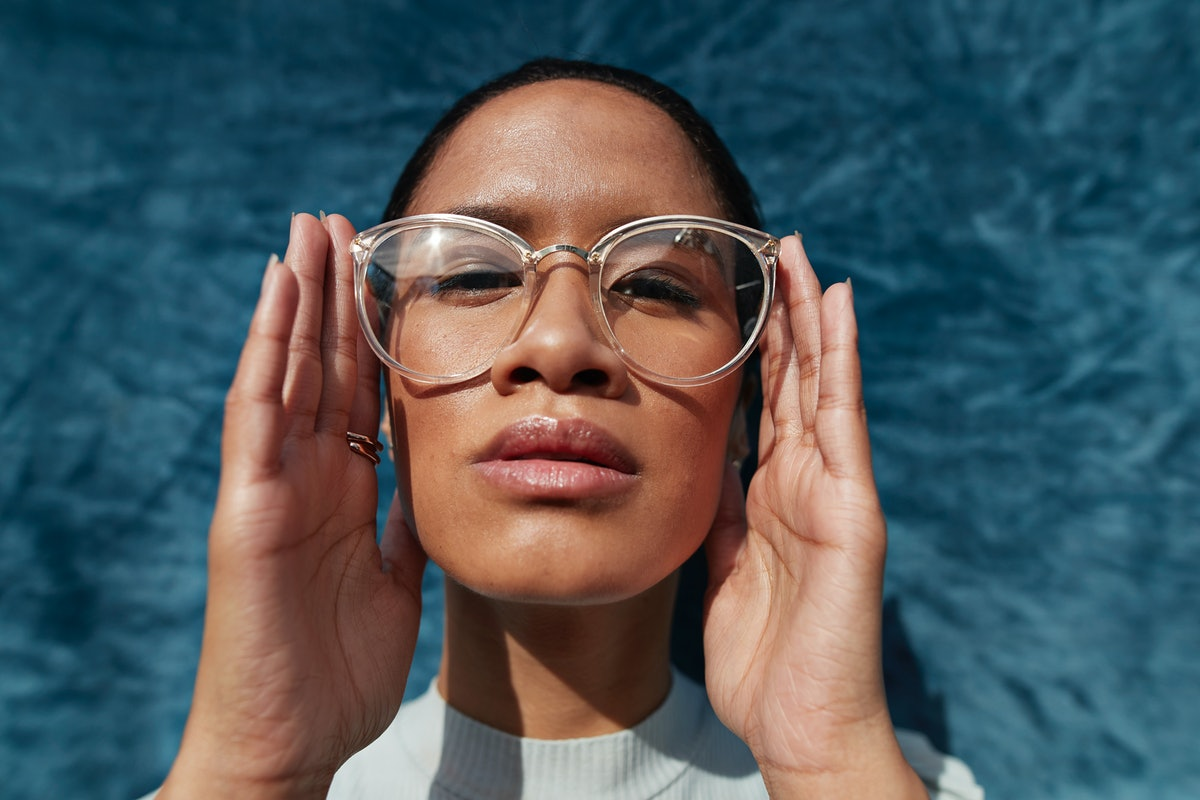 Young woman with big glasses studying the astrology elements and their meanings.