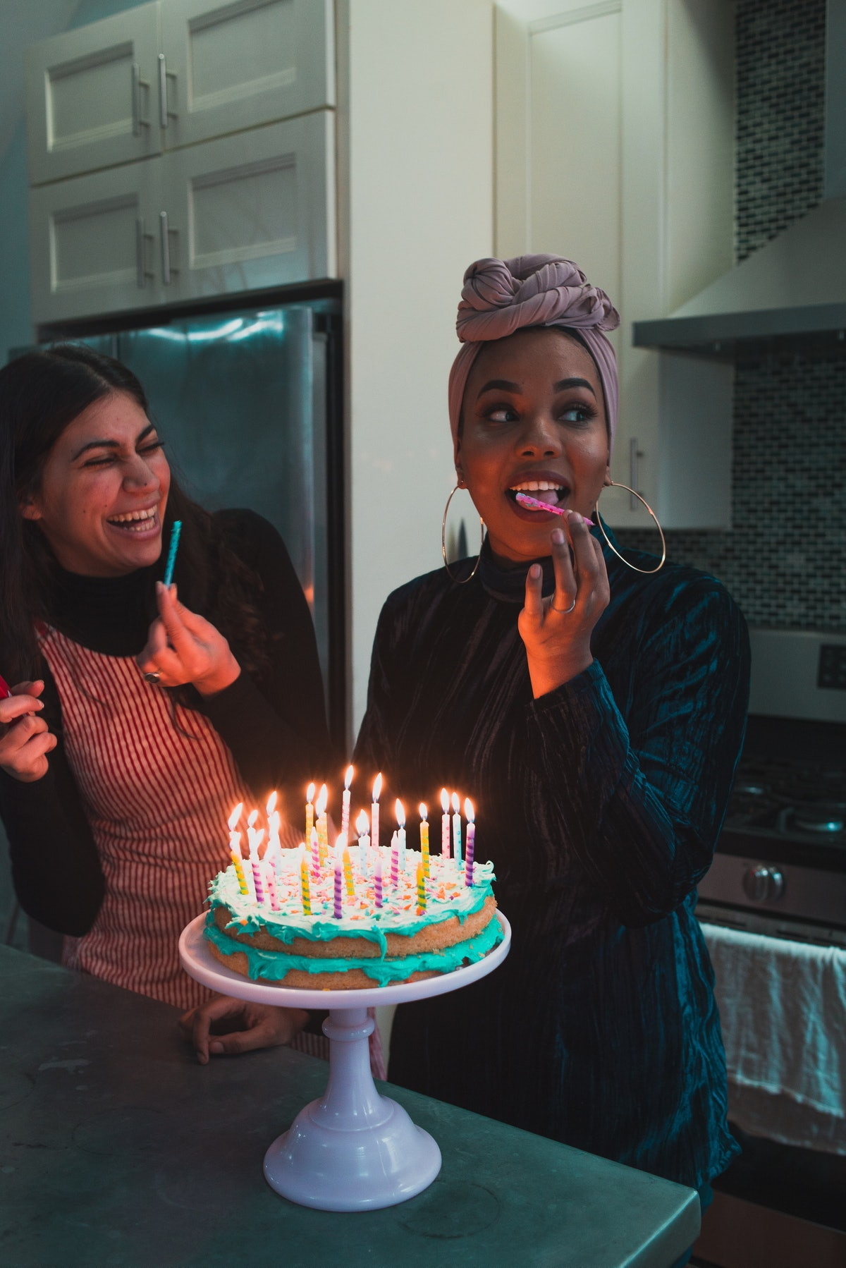 Young woman licking the candle on her birthday cake before posting a happy birthday caption on Instagram.