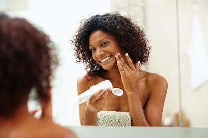 Woman applying sunscreen in the mirror