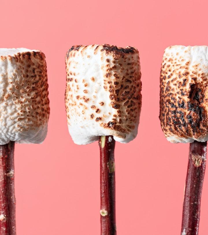 Three toasted marshmallows on sticks