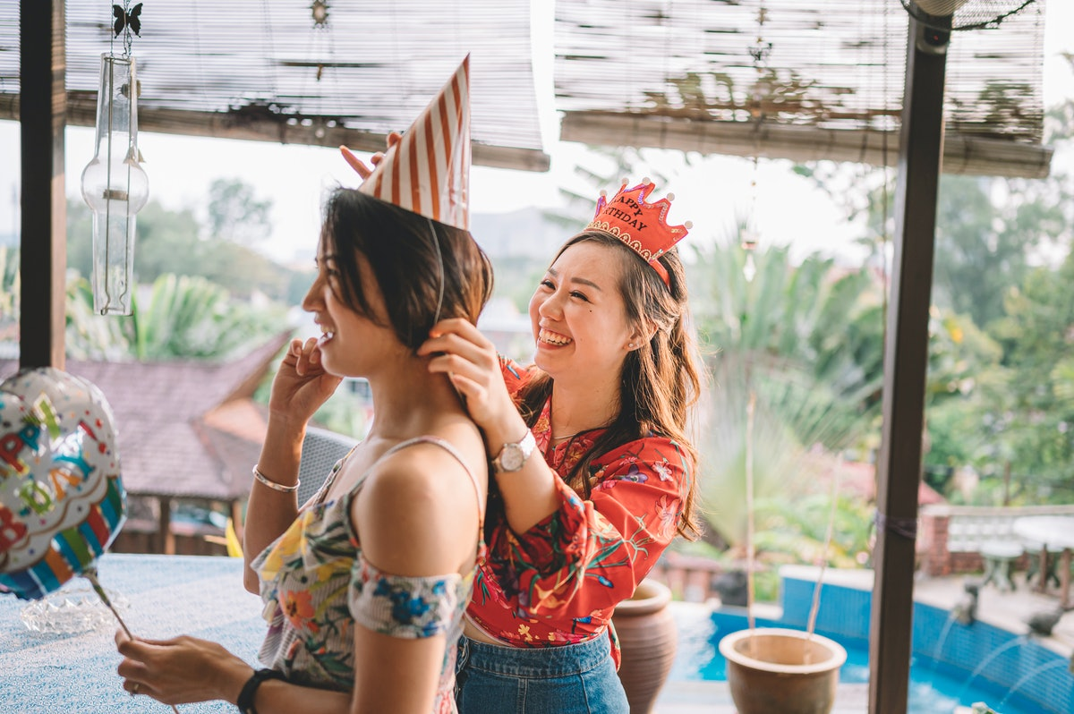 Young friend helping put a party hat on her friend's head before posting a happy birthday caption on Instagram.