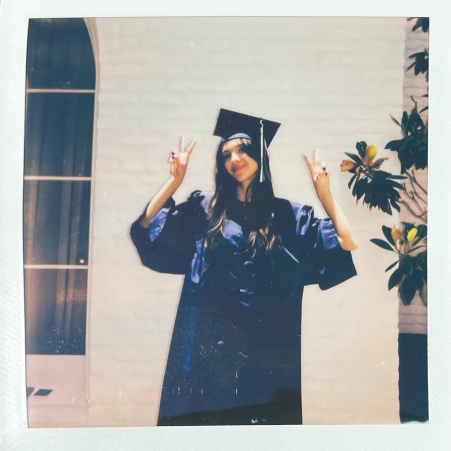 Olivia Rodrigo waves two peace signs in the air while dressed in a graduation cap and gown.