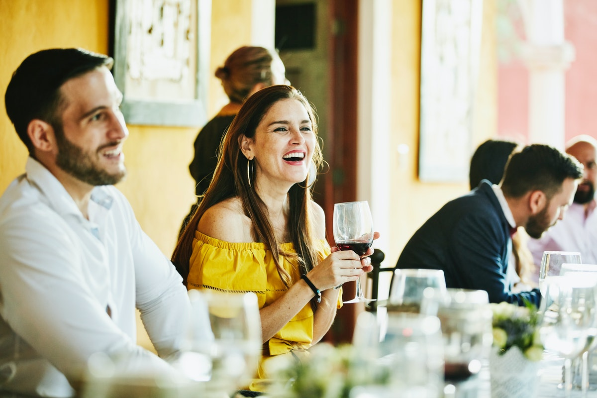 Young woman smiling holding wine at a wedding before posting on social media with Instagram captions...