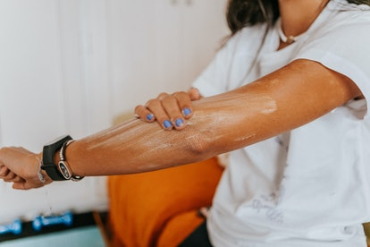 Woman applying sunscreen to her arm