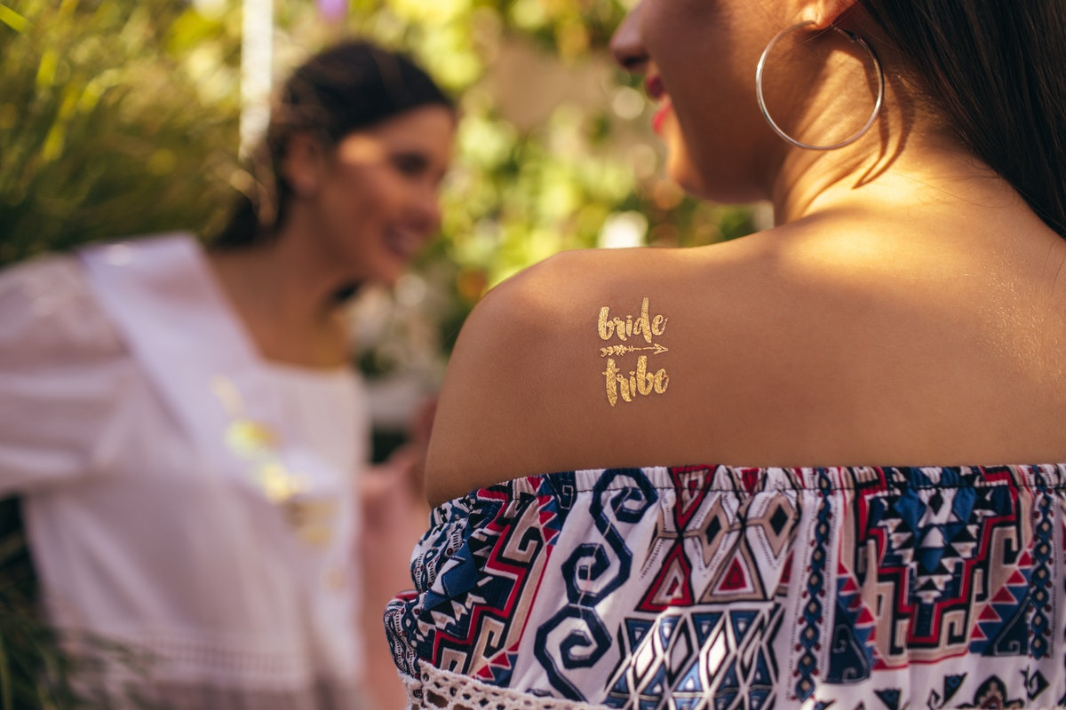 """Woman with """"bride tribe"""" temporary tattoo to pair with bachelorette party captions on Instagram"""