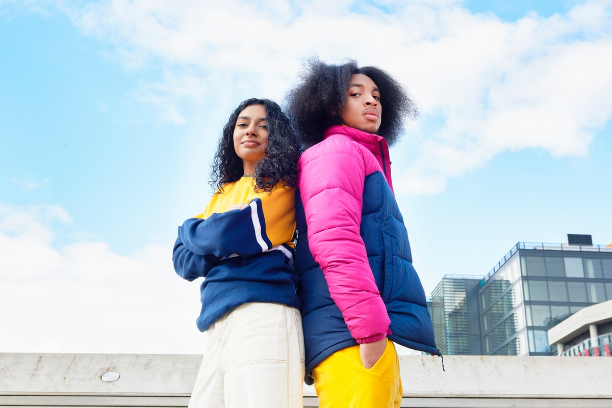 Siblings posing back to back in bright jackets, in need of cute little sister captions to post on In...
