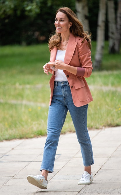 Catherine, Duchess of Cambridge wears white Veja sneakers, blue jeans, and a pink blazer while visiting 'The Urban Nature Project' at The Natural History Museum on June 22, 2021 in London, England.
