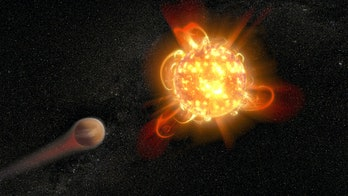 An illustration of a red dwarf star and an orbiting planet.