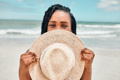 Woman on beach holding a straw hat