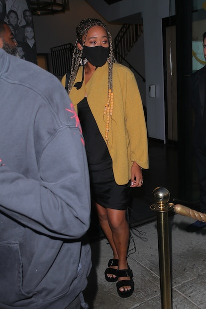 Naomi Osaka wearing a yellow blazer, black dress, and black sandals while on a date night in 2021.