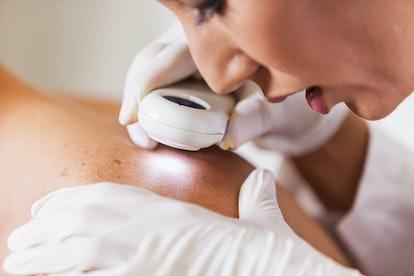 Doctor inspecting skin on shoulder