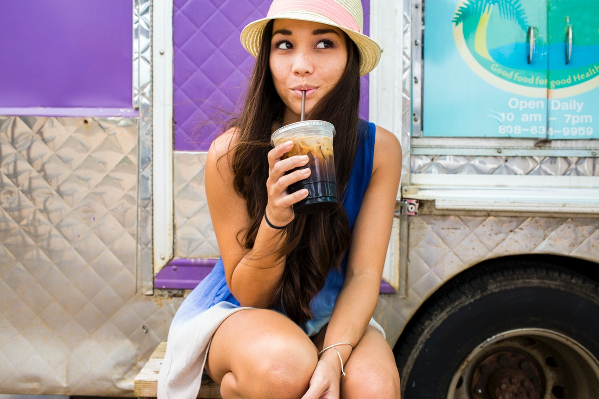 Young women drinking a cold coffee before posting on Instagram with iced coffee captions.