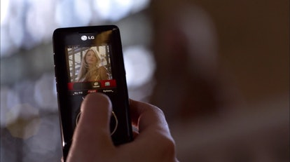 A shot of Blake Lively as Serena in Gossip Girl. She is being photographed from afar through someone's cell phone, which is held up as the focal point of the shot.