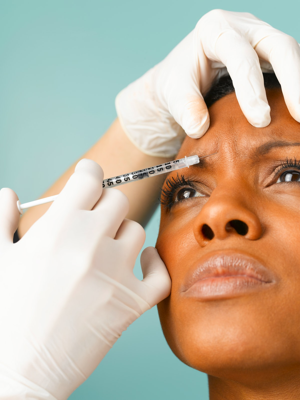 Woman getting a needle injection in forehead