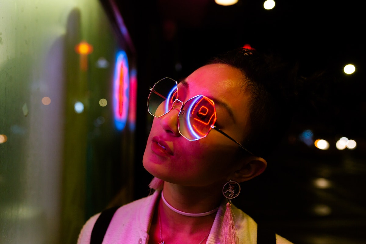 Young woman in neon lights looking up at the moon, thinking what planet rules Tuesday, what planet rules Wednesday, and why Friday is Venus Day.