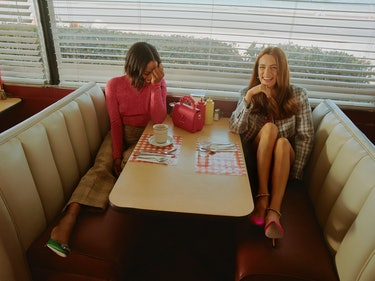 'Zola' stars Taylour Piage and Riley Keough laugh as they sit together in a diner booth.