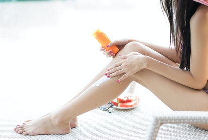 Woman applying sunscreen to legs
