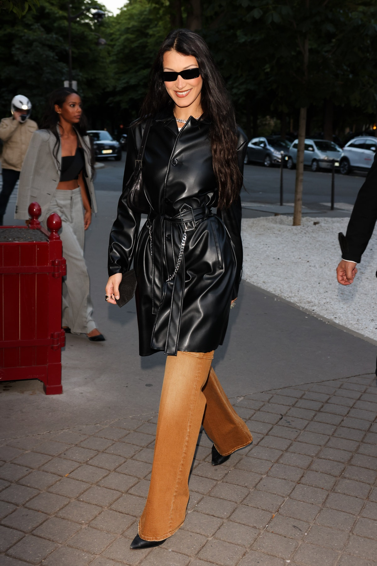 Bella Hadid wearing a leather jacket and burnt orange jeans