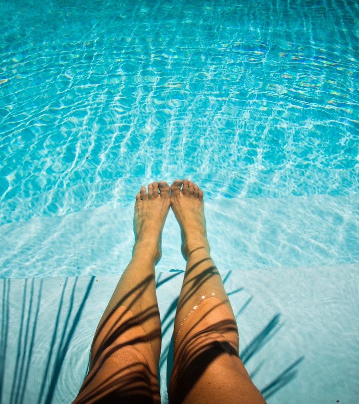 legs floating in pool