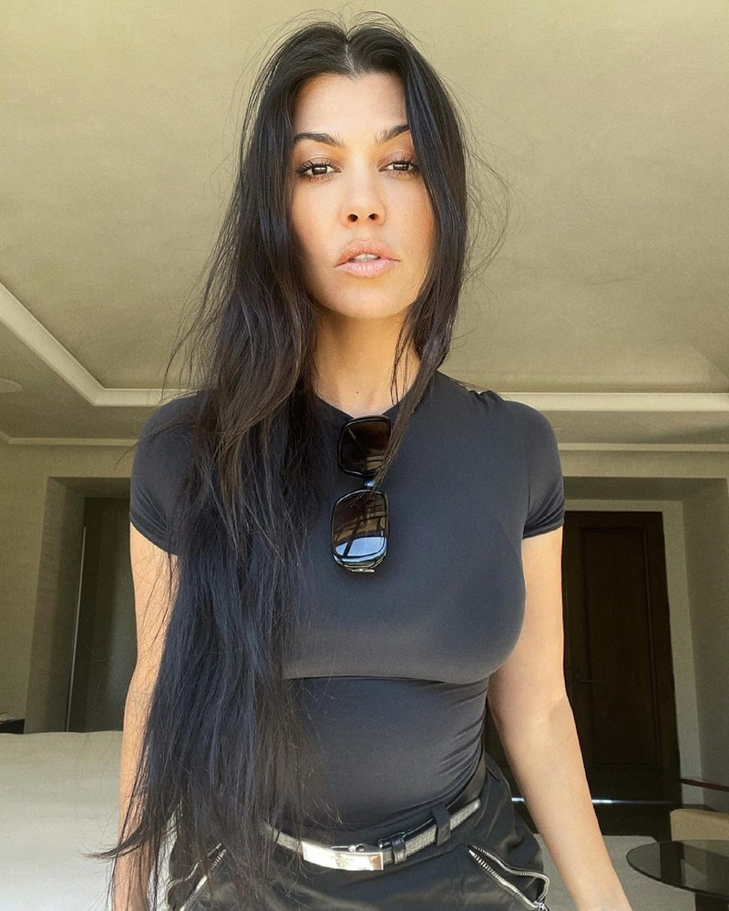 Kourtney Kardashian posing for a photo wearing all black and her hair down