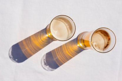 overhead shot of beer glasses on a white table
