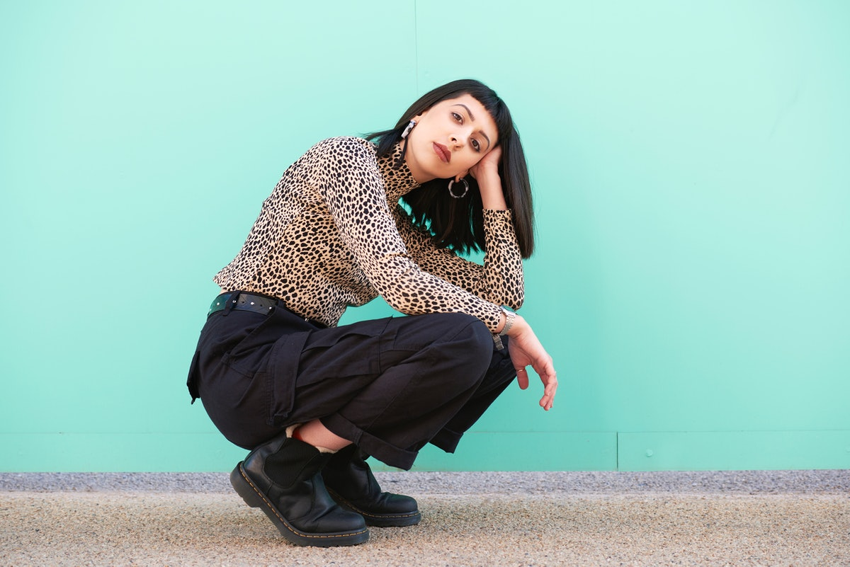 Young woman crouching on the floor in front of a blue wall, feeling bad during the month of July 202...