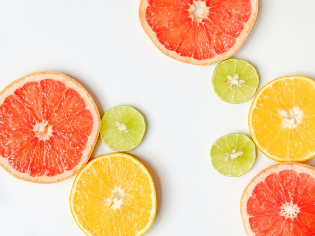 assorted sliced citrus fruits on white background