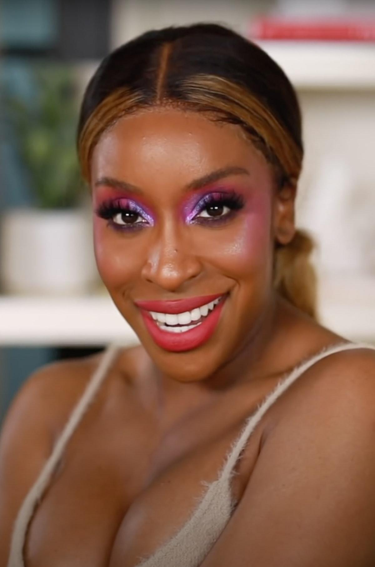 Jackie Aina rocking holographic purple eyeshadow and a rosy blush.