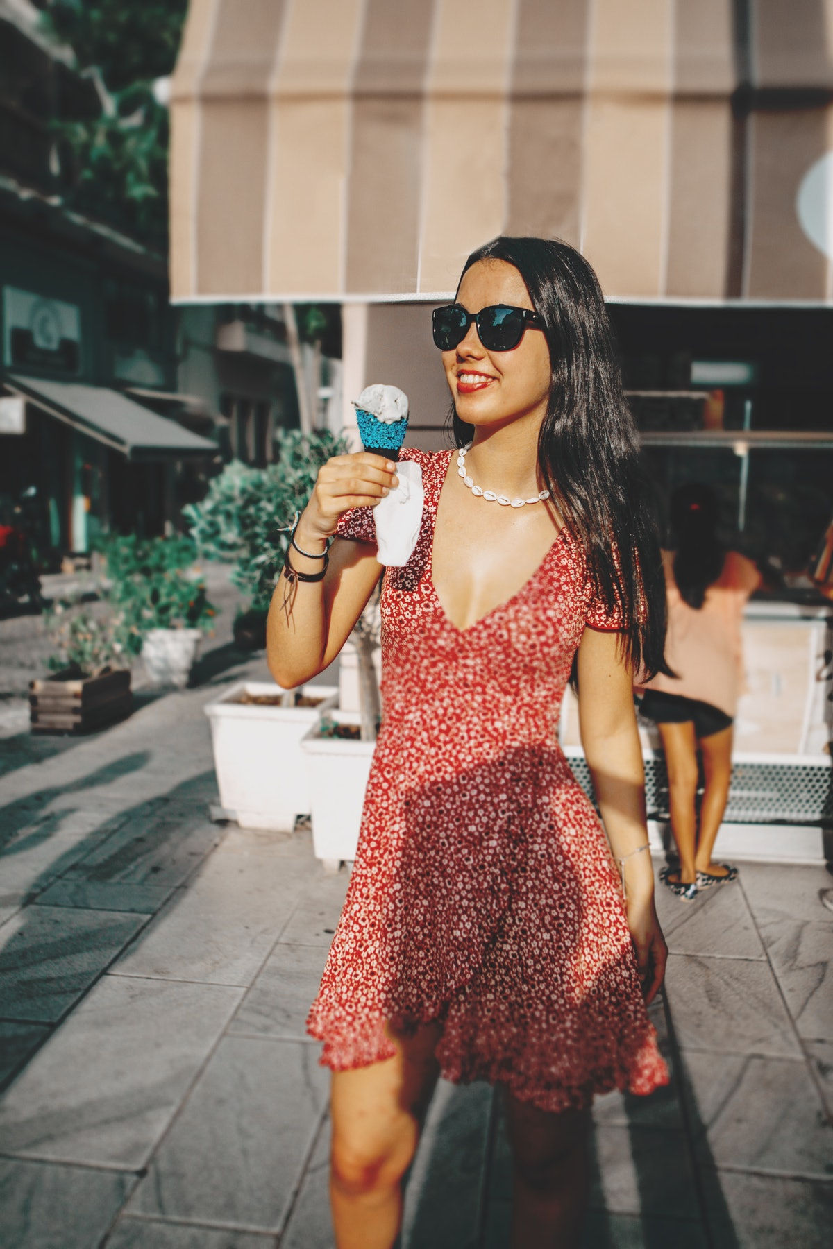 Young woman wearing sunglasses and a summer dress holding an ice cream cone before posting a pic on ...