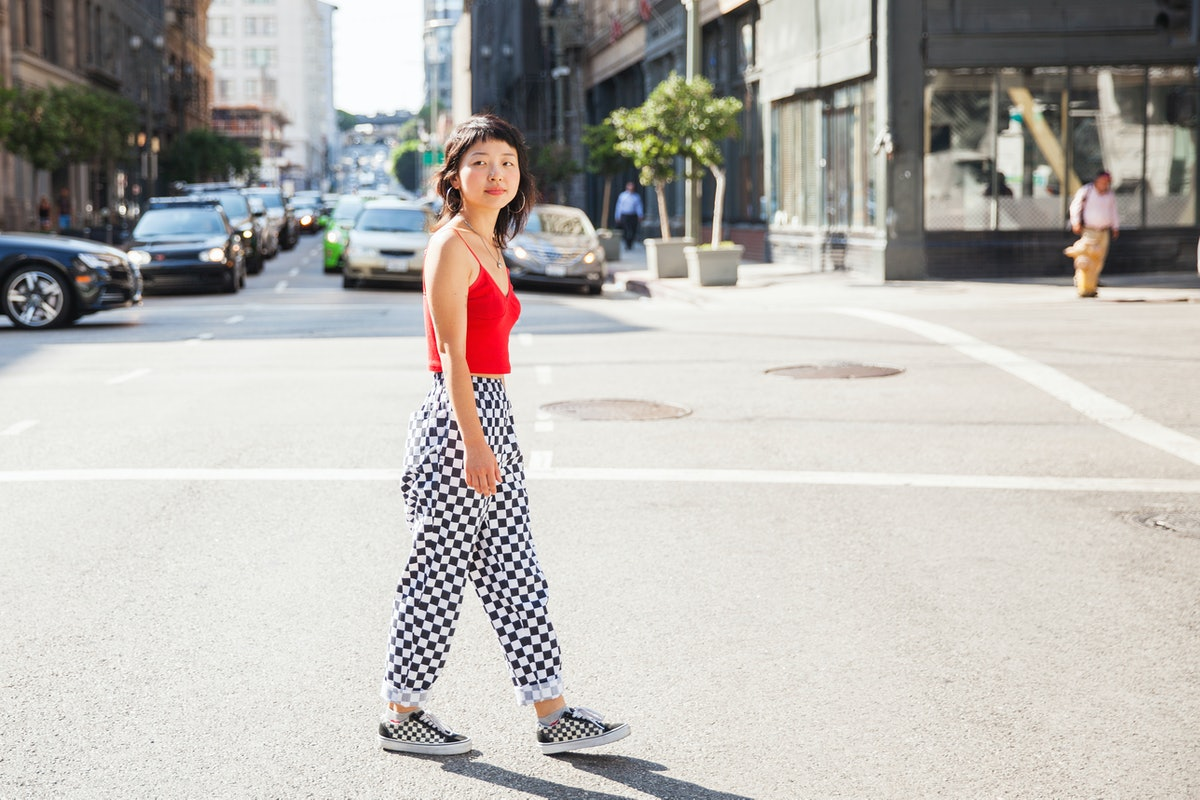 Young woman walking across the street in checked pants, having the worst month of July 2021, per her...