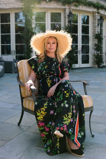 Kathy Hilton sits in a chair outside on a patio wearing a straw hat and a black floral dress.