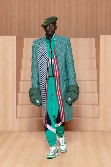 A spring 2022 men's Louis Vuitton model wearing giant gloves