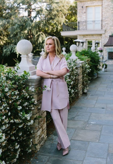 Kathy Hilton wears a blush suit as she stands near a garden while posing for Bustle.