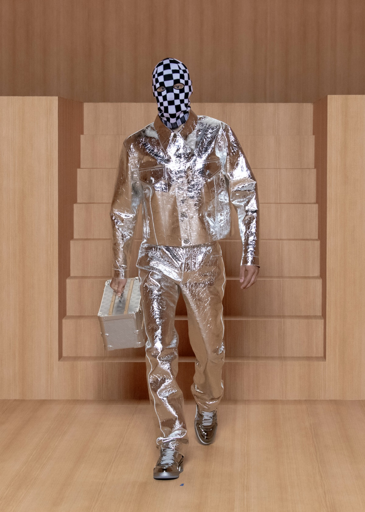 A model wearing a Louis Vuitton men's spring 2022 metallic suit and checkered face covering
