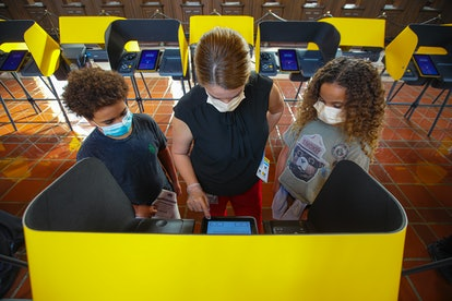 Dyana Elam, center, with her children Jackson Love, 11, left, and Jordan Love, 11, votes at a pollin...