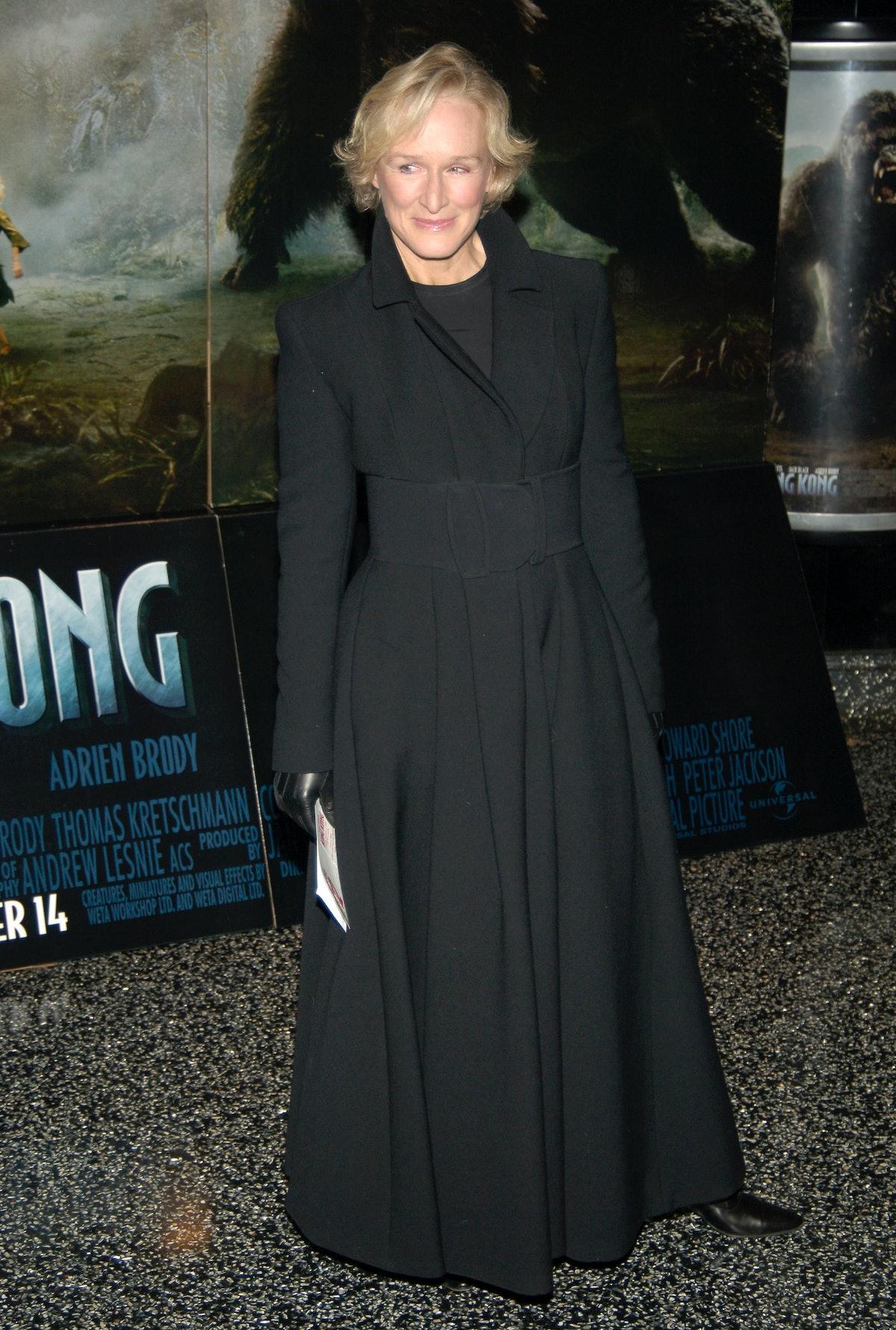 Glenn wearing an all black coat and dress ensemble