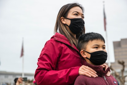 """Minji Wong of San Francisco stands behind her nine-year-old son Miles while attending a """"Love our Pe..."""