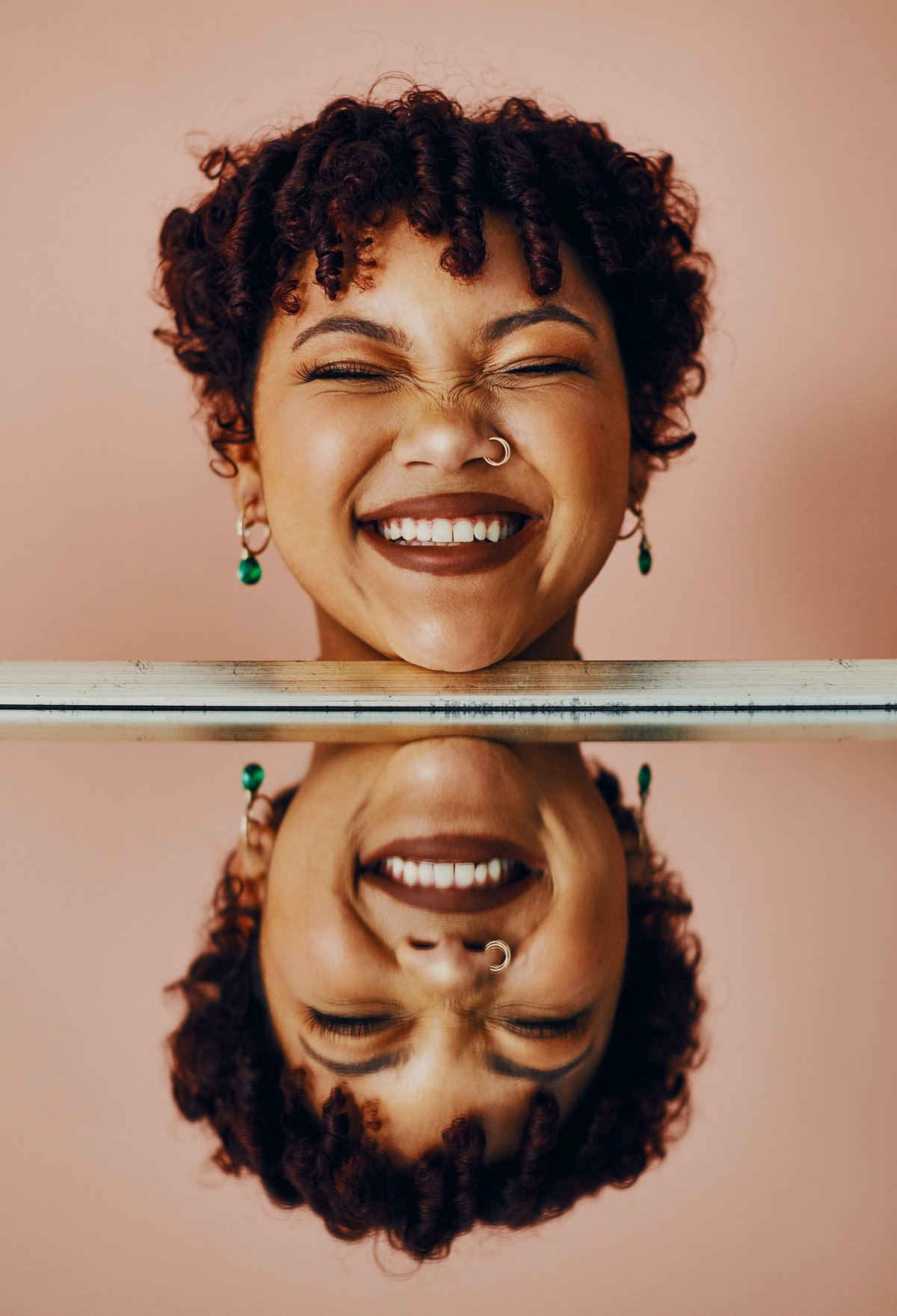 Young woman smiling next to her reflection because of her best July 2021 monthly horoscope.