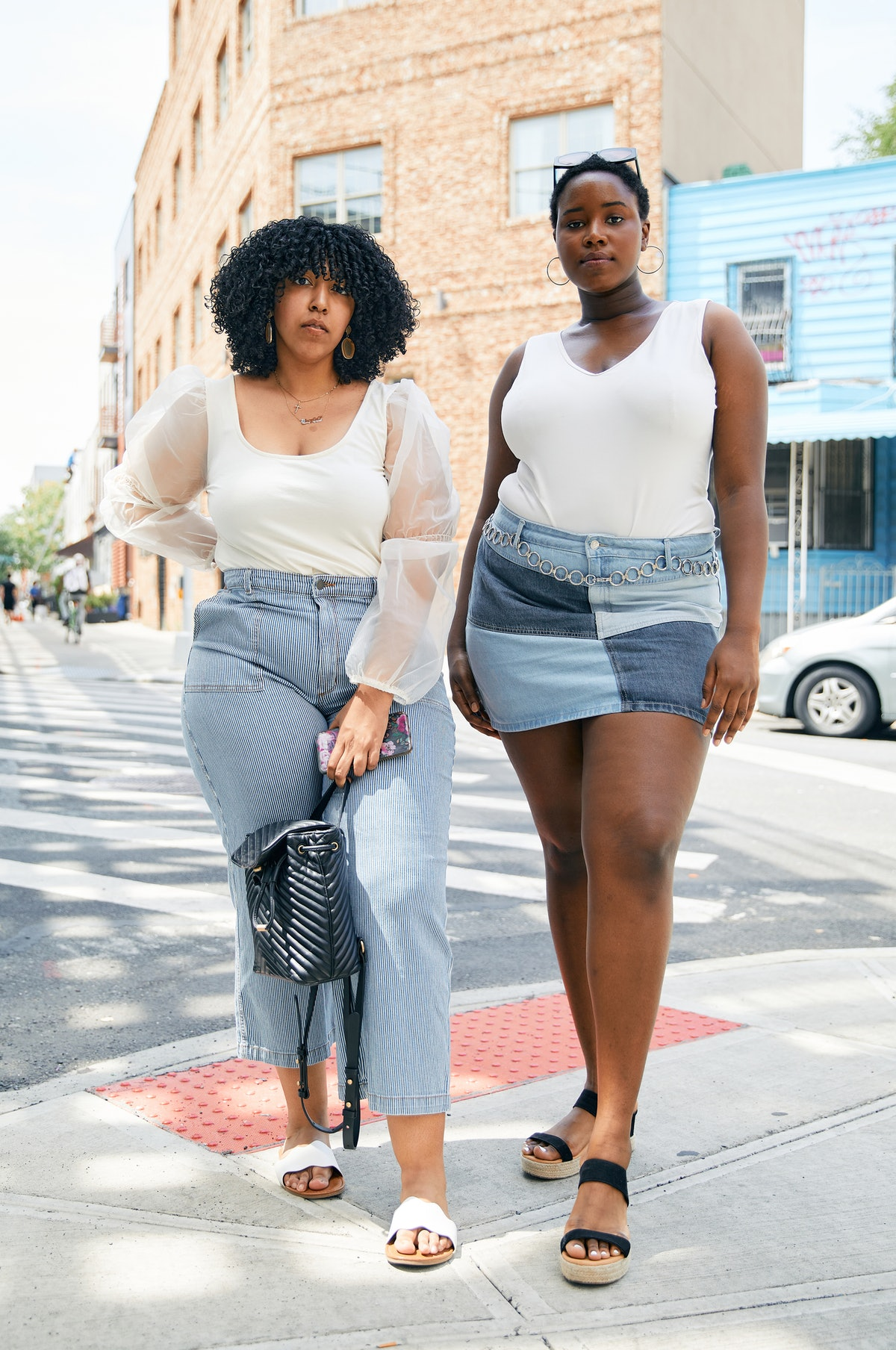 Two plus-size Black women standing on a street corner wearing plus-size white tops and denim bottoms.