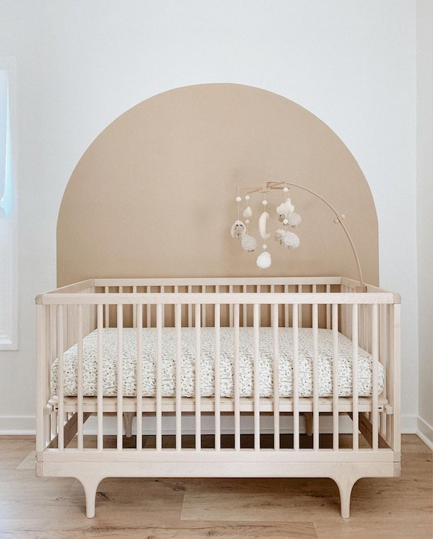 baby nursery with painted arch behind crib