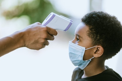 masked child getting his temperature taken at school