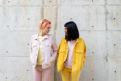 2 best friends with compatible zodiac signs in yellow outfits looking into each other's eyes.