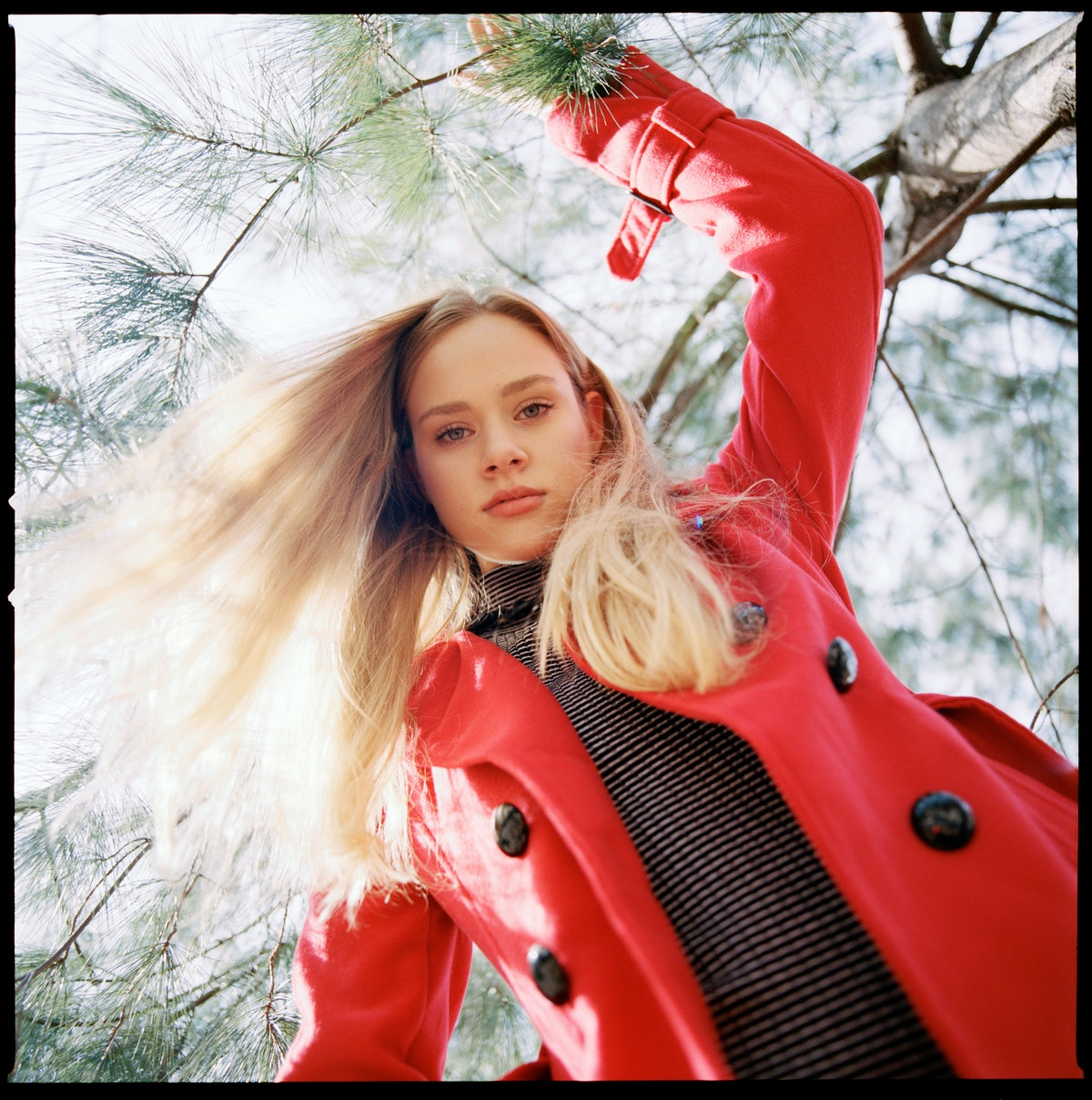 Young woman in red coat, staring down the camera, ready for a fight per her zodiac sign: Cancer.