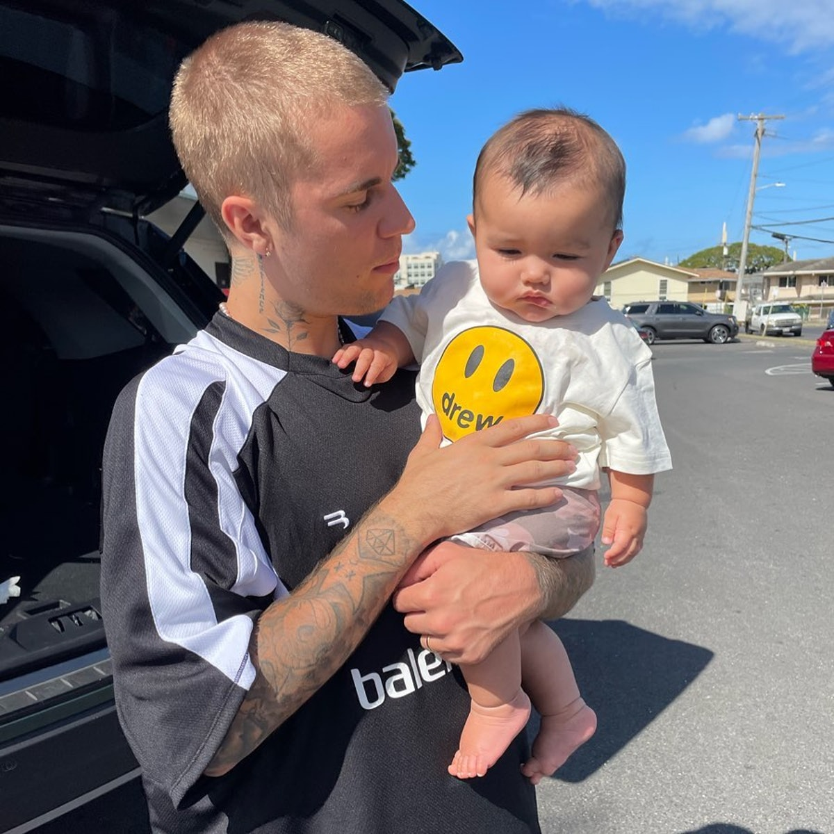 Justin Bieber sporting a buzzcut and holding a baby
