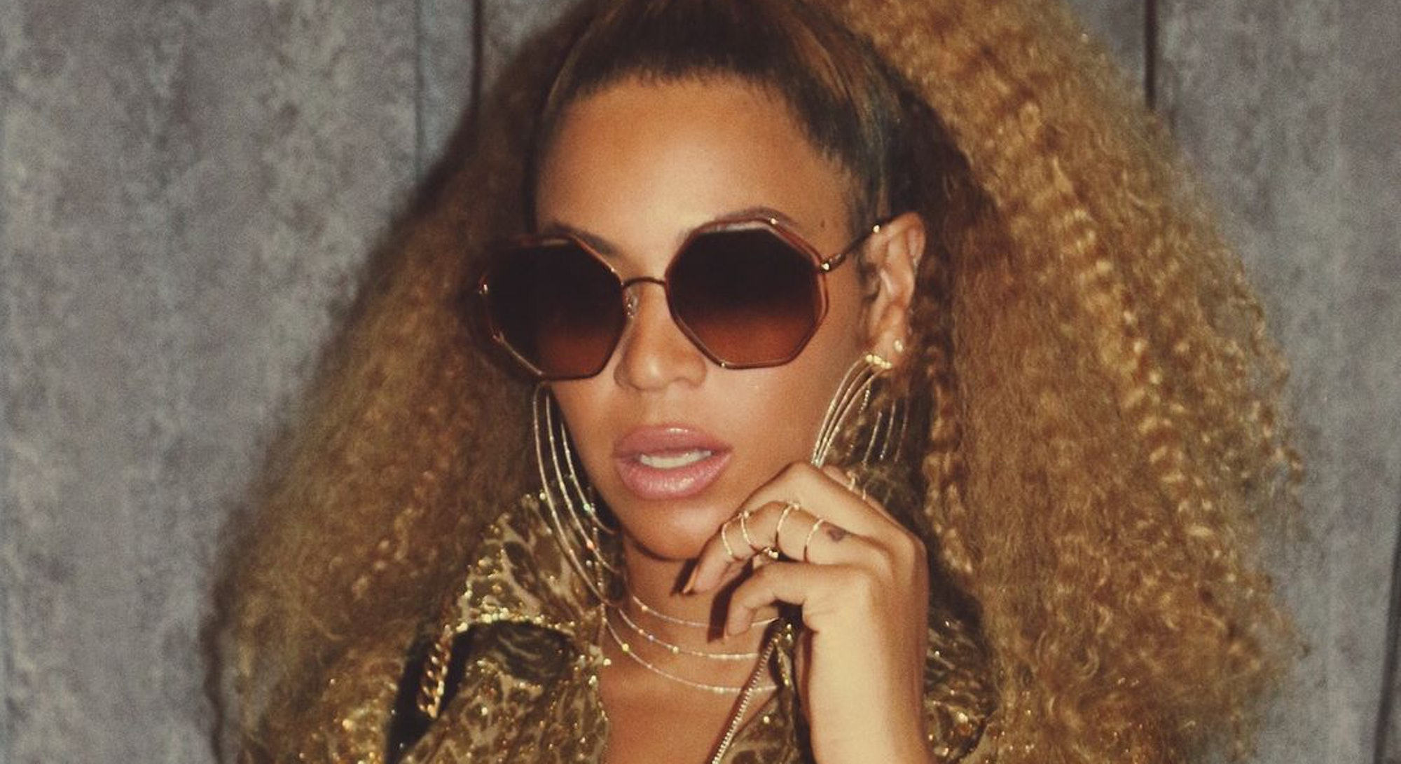Beyoncé in gold with crimped hair posing