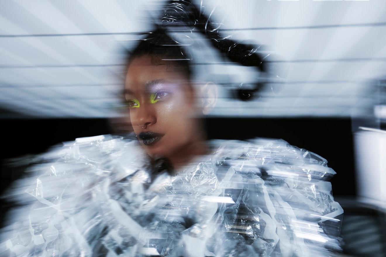 A closeup of Willow Smith wearing neon eyeshadow and a silver Noir Kei Ninomiya coat.