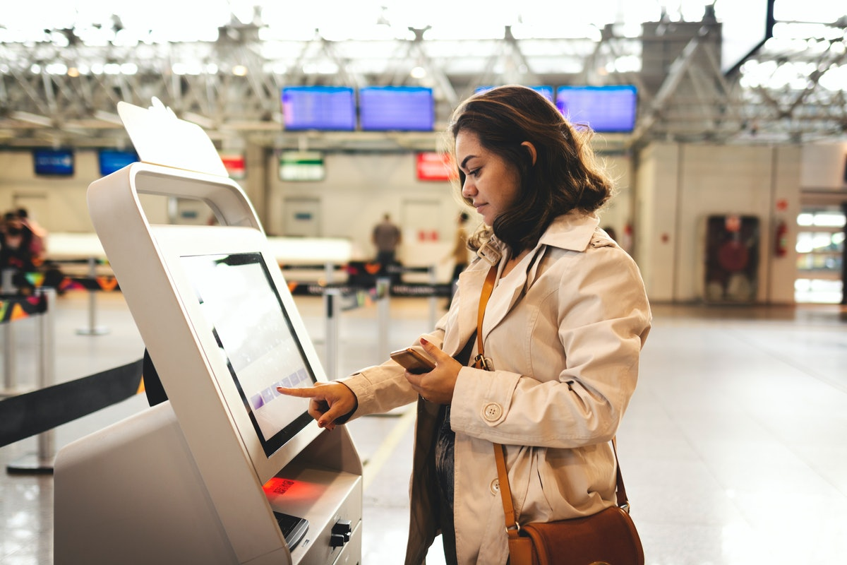 Young woman checking in at an airport on the best day for her to travel in fall 2021, based on her z...