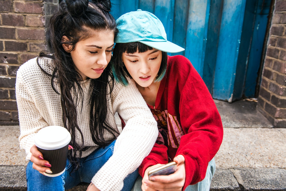 A pair of roommates on a stoop, texting using a funny group chat name.