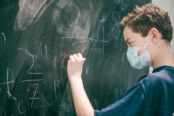 masked student in classroom working out math equations on chalkboard